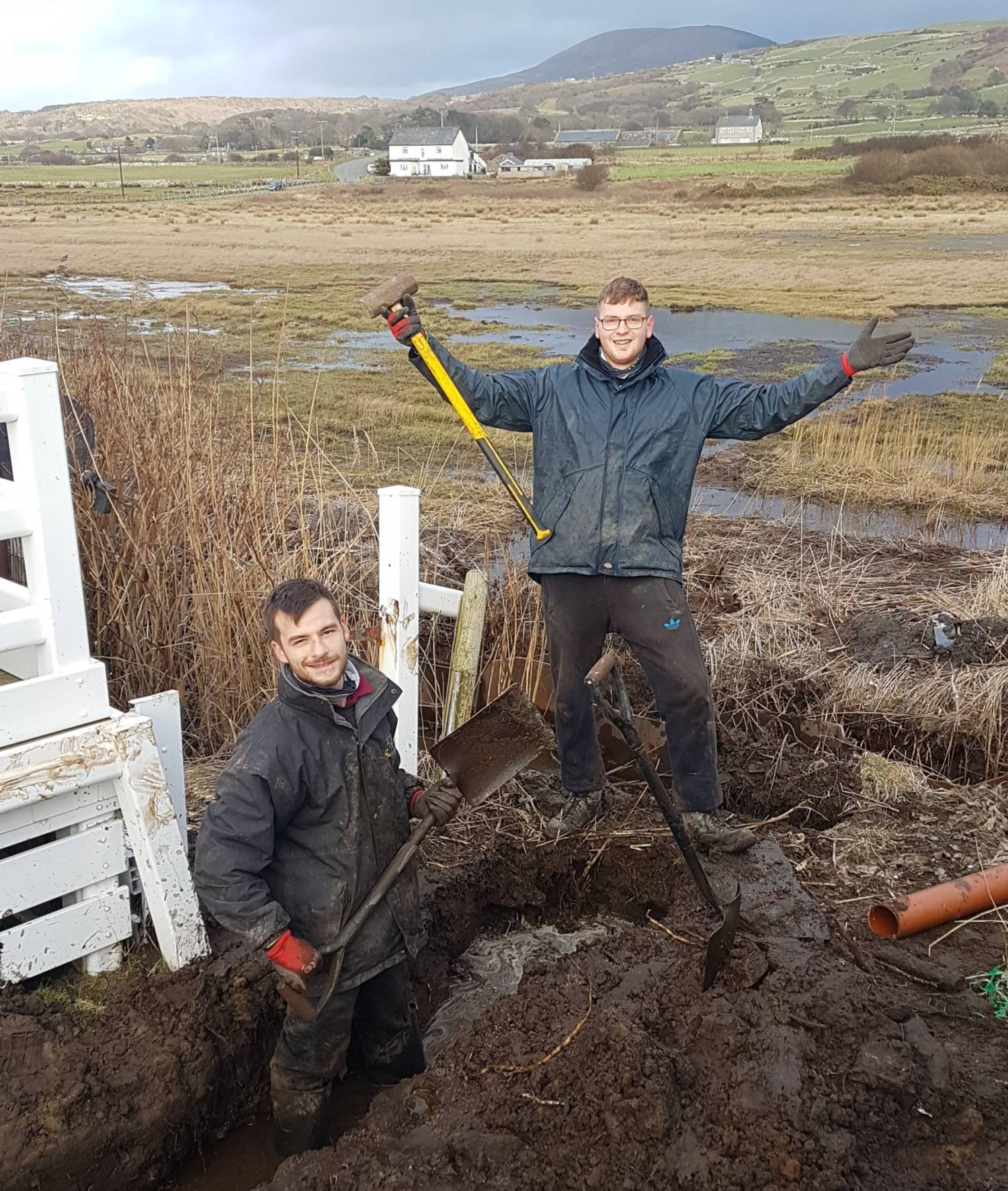 Ricky and george stood digging at Sunnysands caravan park, there are hills in the background and they are smiling.